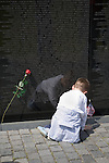 A young boy places a flag to remember a loved one at the Vietnam memorial in Washington D.C. in the United States.