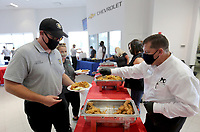 Kris Villines (right), service manager with McLarty Daniel Chevrolet, serves captain Dustin McDonald, with the Springdale Fire Department, a lunch Wednesday, September 9, 2020, hosted by McLarty Daniel Chevrolet and catered by the Catfish Hole restaurant at the dealership in Springdale. The dealership hosts the annual 9/11 meal for all emergency responders and military personnel in the northwest Arkansas area in appreciation of their service and commitment to the community. Check out nwaonline.com/200910Daily/ and nwadg.com/photos for a photo gallery.<br /> (NWA Democrat-Gazette/David Gottschalk)