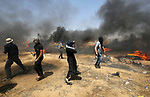 A Palestinian woman uses a slingshot to hurl stones towards Israeli security forces during clashes in tents protest where Palestinians demanding the right to return to their homeland, at the Israel-Gaza border, in Khan Younis in the southern Gaza Strip, on May 11, 2018. Photo by Ashraf Amra