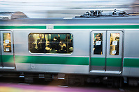 Commuters travel on a train in central Tokyo.