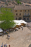 The main town square in Saint Emilion with Cafes with outside seating terrasse with parasols, people drinking and eating in the sun Saint Emilion Village Bordeaux Gironde Aquitaine France
