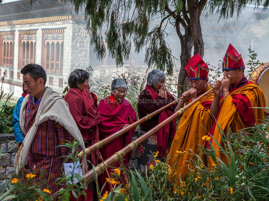 Bumthang, Bhutan.  Monks Playing Trumpets (Dung-chen) Entering Jambay Lhakhang Monastery.