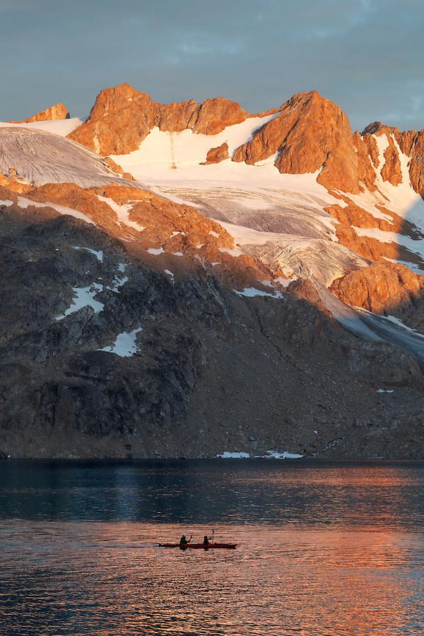 Kayakers paddling in double kayak below mountains at sunset, Sammileq Fjord, Ammassalik Island, East Greenland