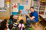 Education preschoool children ages 3-5 male teacher reading pictrue book to group of children seated on rug horizontal
