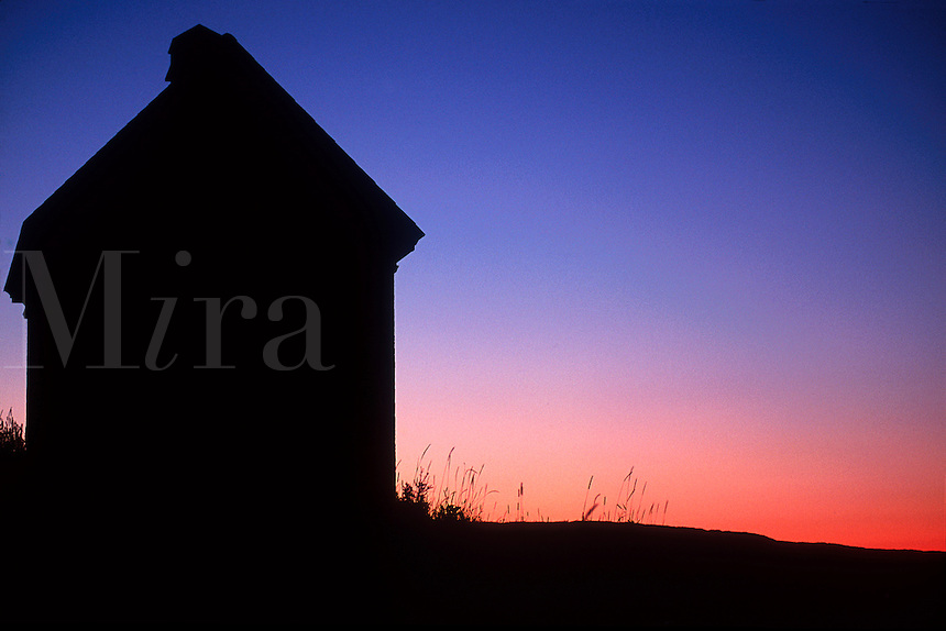 Silhouette of a coastal shack.