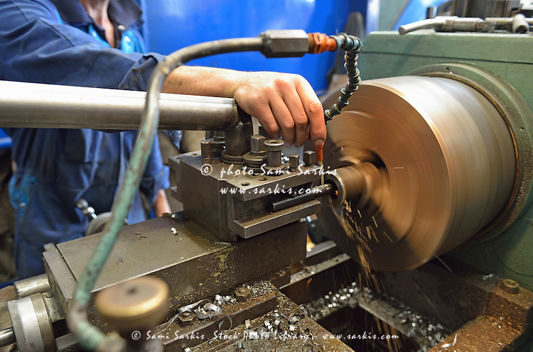 Worker at factory checking a milling cutter, France