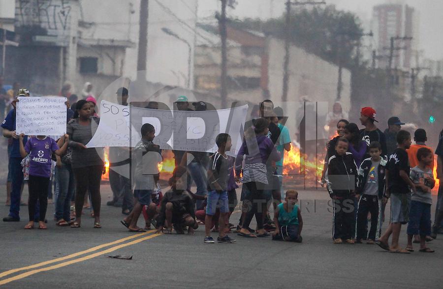 SAO PAULO, SP, 10 JANEIRO 2013 - PROTESTO AREA DE RISCO - Moradores de área de risco no Jardim Guairacá, zona leste de São Paulo, fecharam a rua Costa Barros com uma barricada em protesto realizado nesta quinta-feira. Eles reclamam da ameaça de deslizamentos de terra em suas casas, construídas à beira de um córrego. (FOTO: WILLIAM VOLCOV / BRAZIL PHOTO PRESS).