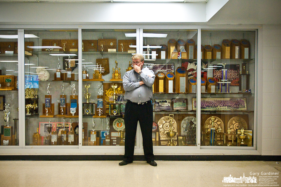 Brad Hayes stands in front of  one of the Westerville High School sports trophy cases as the city's school board meets to consider budget cuts required by the failure of a $23 million levy and tax increase. One of the cuts expected is sports.