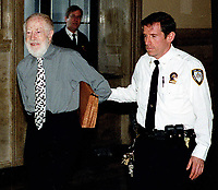 Queens NY 2000_Handcuffed and escorted by officers, 80 year old Abe Hirschfeld, is brought to NY Supreme Court where he is being sued by a group of co-op owners who claim he misappropriated two million dollars.(Photo©Neil Schneider)