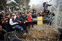 Pictured: Refugees use metal poles to try to bring down the barbed wire gate of the fence Monday 29 February 2016<br /> Re: A crowd of migrants has burst through a barbed-wire fence on the FYRO Macedonia-Greece border using a steel pole as a battering ram.<br /> TV footage showed migrants pushing against the fence at Idomeni, ripping away barbed wire, as FYRO Macedonian police let off tear gas to force them away.<br /> A section of fence was smashed open with the battering ram. It is not clear how many migrants got through.<br /> Many of those trying to reach northern Europe are Syrian and Iraqi refugees.<br /> About 6,500 people are stuck on the Greek side of the border, as FYRO Macedonia is letting very few in. Many have been camping in squalid conditions for a week or more, with little food or medical help.