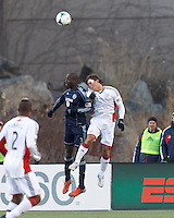 Sporting Kansas City defender Ike Opara (3) and New England Revolution substitute midfielder Ryan Guy (13) battle for head ball.   In a Major League Soccer (MLS) match, Sporting Kansas City (blue) tied the New England Revolution (white), 0-0, at Gillette Stadium on March 23, 2013.