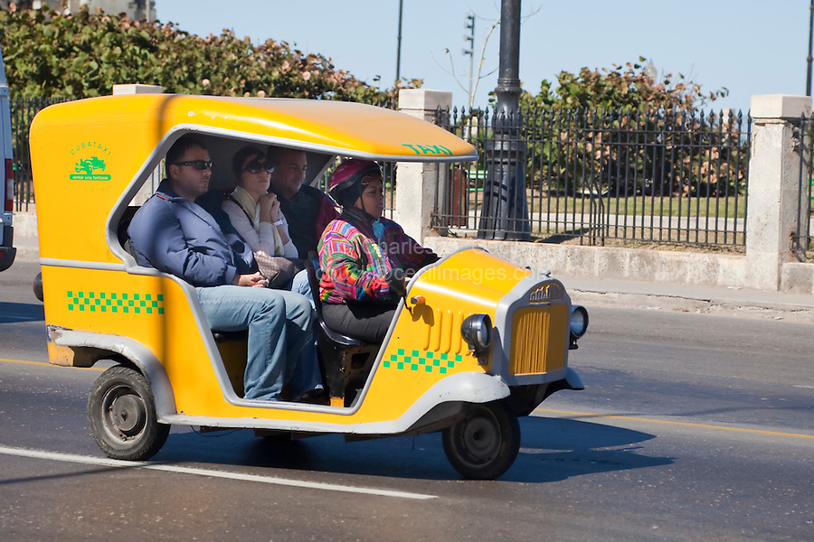 Cuba, Havana.  Three-wheeled Taxi  with Three Passengers and Driver.