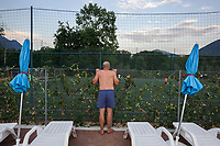 Switzerland. Canton Ticino. Tenero. Camping Campofelice. A swiss german bald man looks over the fence and watches the football tournament from the pool side. The man wears a blue swimsuit.19.07.2018 © 2018 Didier Ruef