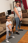3 year old boy at home with mother, lifting weights with her