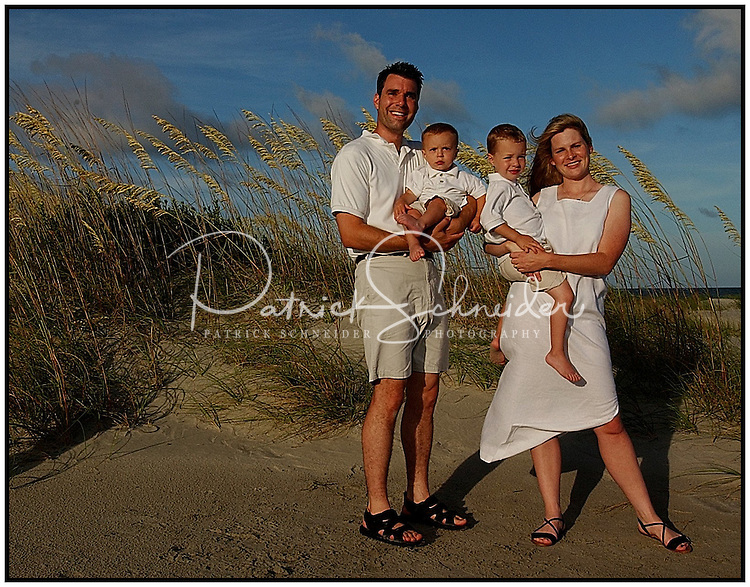 A family poses at the beach for a family portrait. Model released image.