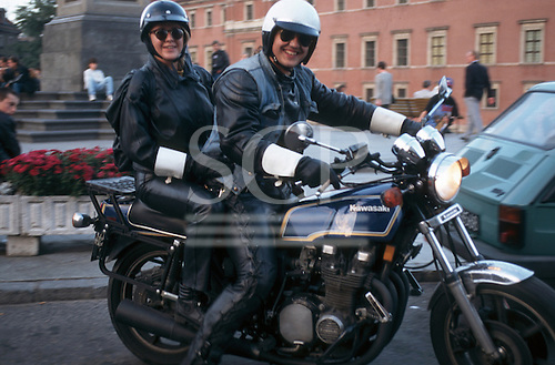 Poland. Two people in leather outfit and wearing a helmet on a Kawasaki motorbike.