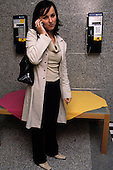 Bosnia and Herzegovina. Young woman standing by payphones (PTT BIH) talking on her mobile; small table with table cloth.