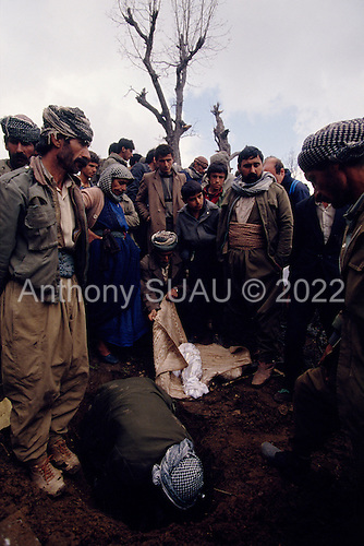Isikveren, Turkey.April 12, 1991..At one of three camp grave sights a family buries a child that died in the night. A mountain top Kurdish refugee camp became home to an estimated 300,000 refugees after they fled Saddam Hussein's post Gulf war persecution...In the wake of the 1991 Persian Gulf War rebellions in Southern and Northern Iraq occurred. The uprising in the Kurdish areas of Northern Iraq broke out in March, sparked by demoralized Iraqi Army troops returning from it's defeat against United States lead coalition forces in southern Iraq and Kuwait. Although they presented a threat to Iraqi President Saddam Hussein?s regime, his Iraqi Republican Guard suppressed the rebellion with massive force, as the expected US intervention never materialized. ..The faltering rebellion fueled a terrified mass exodus. The U.N. High Commissioner for Refugees called it the largest in its 40?year history. During March and early April, nearly two million of Iraqis escaped from strife-torn cities to the mountains along the northern borders and into Turkey and Iran. Their exodus was sudden and chaotic, with thousands fleeing on foot, on donkeys, or crammed onto open-backed trucks and tractors. Thousands, many of them children, died or suffered injury along the way, primarily from adverse weather, unhygienic conditions and insufficient food and medical care. Some were killed by army helicopters, which deliberately strafed columns of fleeing civilians. Others were injured when they stepped on land mines planted by Iraqi troops near the Iran border during the war. Greenpeace has estimated that at one point in 1991, an estimated 2,000 Kurds were dying every day..