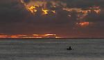 A local i-kiribati paddles during a magnificent sunset on the remote island of Kiritimati in Kiribati.