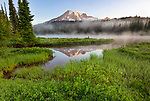 Mount Rainier National Park, WA: Morning light on Mount Rainier with still reflection and mist rising at Reflection Lakes