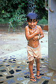 Koatinemo Village, Brazil. Assurini indian child having a shower in the newly-erected village shower.