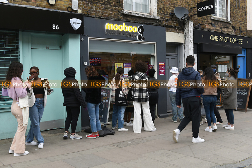 People queue for takeaway food and drinks in Camden Town as the COVID-19 lockdown restrictions start to ease across the UK on 2nd April 2021