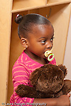 Education Preschool first days of school 2-3 year olds girl holding favorite stuffed animal and using pacifier