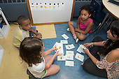 MR / Schenectady, NY. Zoller Elementary School (urban public school). Kindergarten classroom. Student teacher reviews Spanish language flashcards with a small group of native Spanish speakers. MR: She4, Car38, Cas12, Fue3. ID: AM-gKw. © Ellen B. Senisi.