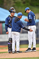 Asheville Tourists pitching coach Mark Brewer has a meeting on the mound with starting pitcher Riley Pint (27) and catcher Willie MacIver (23) during game one of a double header against the West Virginia Power at McCormick Field on April 20, 2019 in Asheville, North Carolina. The Tourists defeated the Power 12-7. (Tony Farlow/Four Seam Images)