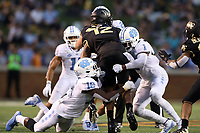 WINSTON-SALEM, NC - SEPTEMBER 13: Jamie Newman #12 of Wake Forest University is sacked by D.J. Ford #16 and Myles Dorn #1 of the University of North Carolina during a game between University of North Carolina and Wake Forest University at BB