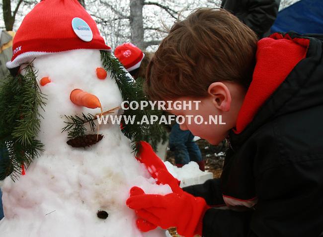 ede 250207 nederlands kampioenschap sneeuwpoppenbouwen.<br />dit deelnemertje legt in de stromende regen de laatste hand aan zijn alweer wegkwijnende sneeuwpop<br />Foto Frans Ypma APA/foto
