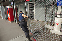 Switzerland. Canton Ticino. Lugano. Railway station. A police officer from TPO (Transport Police) is pulling a protective metal fence before the arrival of a chartered train with the supporters of the FC Luzern football club. TPO (Transport Police) is the Swiss Federal Railways Police. Swiss Federal Railways (German: Schweizerische Bundesbahnen (SBB), French: Chemins de fer fédéraux suisses (CFF), Italian: Ferrovie federali svizzere (FFS)) is the national railway company of Switzerland. It is usually referred to by the initials of its German, French and Italian names, as SBB CFF FFS.  2.06.2017 © 2017 Didier Ruef