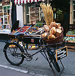 Netherlands, North Holland, Amsterdam: Bicycle with basket of bread and corn | Niederlande, Nordholland, Amsterdam: Holland-Fahrrad vor Baeckerei mit Brot und Getreide