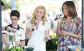 United States first lady Michelle Obama (R) makes a healthy drink with comedian Peyton List and Cameron Boyce (L)  from the comedy series Jessie during the annual White House Easter Egg Roll on the South Lawn of the White House April 21, 2014 in Washington, DC. President Barack Obama and first lady Michelle Obama hosted thousands of people during the annual celebration of Easter. <br /> Credit: Olivier Douliery / Pool via CNP