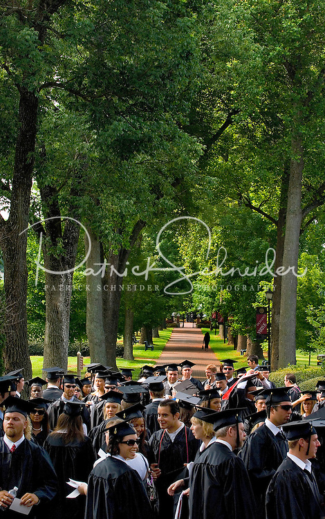 Students gather under the shade of trees in full green cover gather for a graduation ceremony at a college in Belmont, NC.