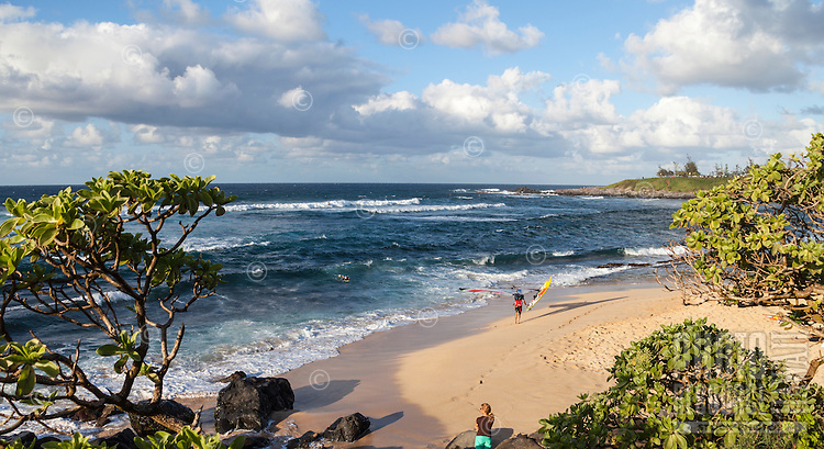 A woman looks out to sea at Ho'okipa Beach, Maui; in the distance, a windsurfer carries his board and a surfer starts in on a wave.