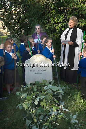 Old Mans Day Braughing Hertfordshire UK. October 2nd 2015. The Rev'd Julie Gawthrope and children from Jenyns First School around the grave of Mathew Wall. Brambles have been placed on the grave as directed in his will to prevent cattle grazing over it. A short service is held while the church bells tolled for a funeral, and then a wedding peal is rung.