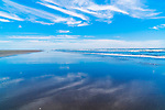 Blue skies reflect in wet sand and surf along Grayland Beach, Washington.  Grayland Beach Stae Park.