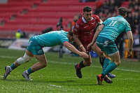 Kieron Fonotia of the Scarlets (C) is brought down by Dan Goggin of Muster (L) during the Guinness Pro14 Round 17 match between the Scarlets and Munster Rugby at the Parc Y Scarlets Stadium, Llanelli, Wales, UK. Saturday 02 March 2019