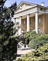 The impressive portico of a neo-classical, Dutch country house, complete with an ornately carved pediment and sweeping stone staircase