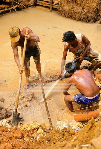 Mucajai, Roraima State, Brazil. Three goldminers at work digging.
