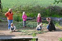 Bau eines Weidenzauns für den Schulgarten, Garten der Grundschule Nusse wird als Projektarbeit von einer 1. Klasse gestaltet, Kinder schneiden Weidenruten, um diese zu einem lebenden Zaun zu verarbeiten, Weidenzaun, Gartenarbeit