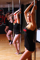 Pictured: Organiser Lisa Broughton (3rd L) with other pole dancers. Saturday 22 February 2014<br /> Re: Eight women have attempted to set a new world record of most people pole dancing at the same time.<br /> Pole 4 Life world record attempt was organised by Lisa Broughton at her Pole Twisters dance studio in Cardiff.<br /> The women had to pole dance for six minutes to set the new record.