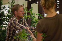 """Two students work to artfully wrap a vine around a post at Orange Coast College's Ornamental Horticulture Club's in-progress installation at the 2012 South Coast Plaza Spring Garden Show in Costa Mesa, CA.  The theme for this year's show is """"healing gardens"""", and the OCC team is installing a """"garden for the blind,"""" which will be complete with a braille world globe and braille labels.  This picture was taken Tuesday April 25, 2012 at ~11pm, as the team was working frantically to meet their Thursday-morning deadline.  This image was taken at a high ISO using the ambient light in the dim mall, so it's noisier than my typical images (and thus I'd recommend against printing it large)."""