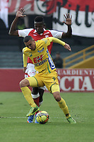 BOGOTA - COLOMBIA -10 -11-2013: Julian Quiñonez (Izq.) mediocampista de Independiente Santa Fe disputa el balón con Luis Paez (Der.) jugador del Atletico Huila, durante del partido por la fecha 18 de la Liga Postobon II-2013, jugado en el estadio Nemesio Camacho El Campin de la ciudad de Bogota. / Julian Quiñonez (R) midfielder  of Independiente Santa Fe vies for the ball with Luis Paez (C) player of Atletico Huila during a match for the 18 date of the Postobon Leaguje II-2013 at the Nemesio Camacho El Campin Stadium in Bogota city, Photo: VizzorImage  / Luis Ramirez / Staff.