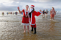 Pictured: Two women dressed as Santa splash about in the water. Tuesday 26 December 2017<br /> Re: Hundreds took part in this year's Boxing Day Walrus Dip which see people in fancy dress taking to the sea at Cefn Sidan beach in Pembrey Country Park, west Wales, UK.