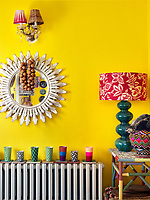 One wall of the yellow-painted kitchen/dining room displays an eclectic collection of furniture and objects