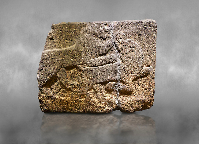 Hittite monumental relief sculpted orthostat stone panel of a Procession. Basalt, Karkamıs, (Kargamıs), Carchemish (Karkemish), 900-700 B.C. Anatolian Civilisations Museum, Ankara, Turkey. Two animals struggling with each other. The lion attacking the bull holds the bull's chin and turns it backwards.  <br /> <br /> Against a grey art background.