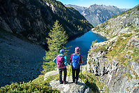 Hiking the Via Alta Via Maggia, a difficult week long trek from Locarno to Broglio, Switzerland. Two hikers stand looking at the Lago di Tome.