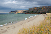 A late autumn view of beautiful Miners Beach with the sun partially lighting up the distant cliffs of Pictured Rocks. Munising, MI